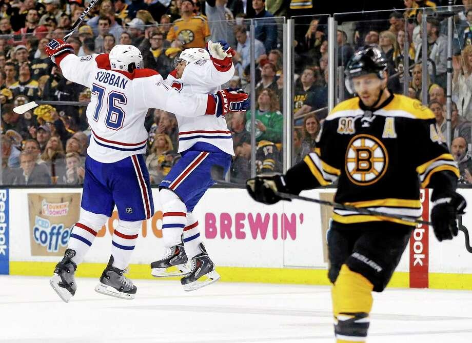 Canadiens defenseman Francis Bouillon jumps with defenseman P.K. Subban (76) to celebrate his goal as Boston Bruins center David Krejci, right, skates away during the third period Thursday. Photo: Elise Amendola — The Associated Press  / AP
