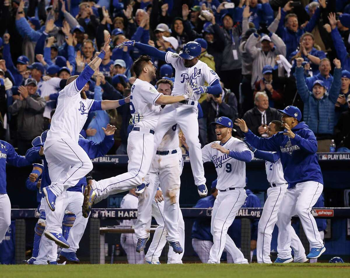 Kansas City Royals celebrate after Alcides Escobar (2) scored on a sacrifice fly by Eric Hosmer during the 14th inning of Game 1 of the Major League Baseball World Series against the New York Mets Wednesday, Oct. 28, 2015, in Kansas City, Mo. (AP Photo/Matt Slocum)