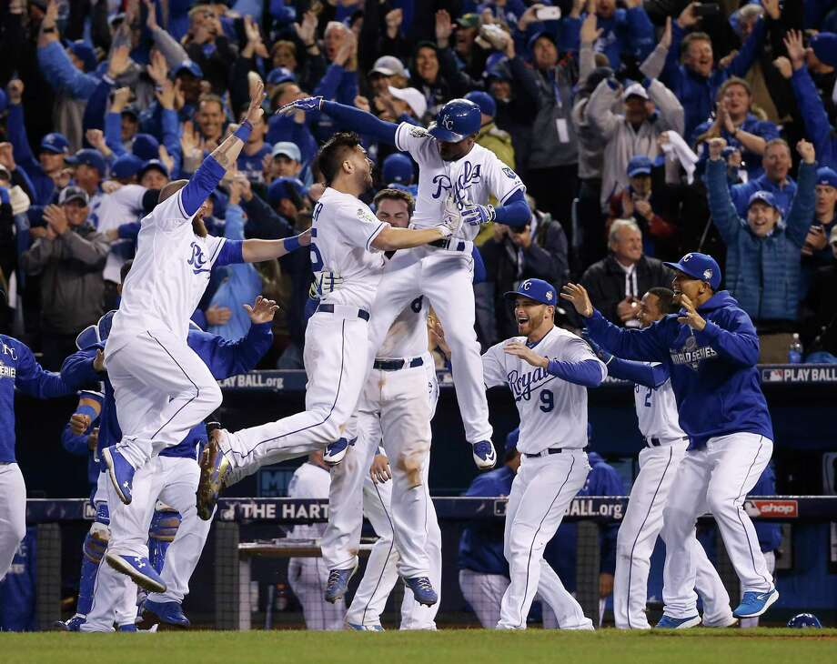 Kansas City Royals celebrate after Alcides Escobar (2) scored on a sacrifice fly by Eric Hosmer during the 14th inning of Game 1 of the Major League Baseball World Series against the New York Mets Wednesday, Oct. 28, 2015, in Kansas City, Mo.  (AP Photo/Matt Slocum) Photo: AP / AP