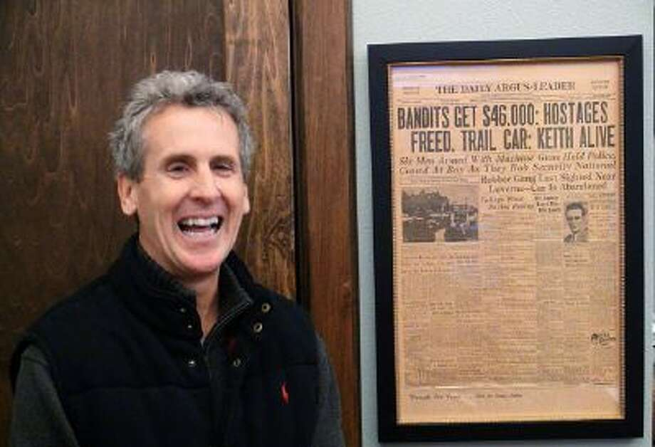 Pierce McDowell at South Dakota Trust in Sioux Falls, with a 1934 news clipping from when a notorious gang robbed the bank where his grandfather worked.