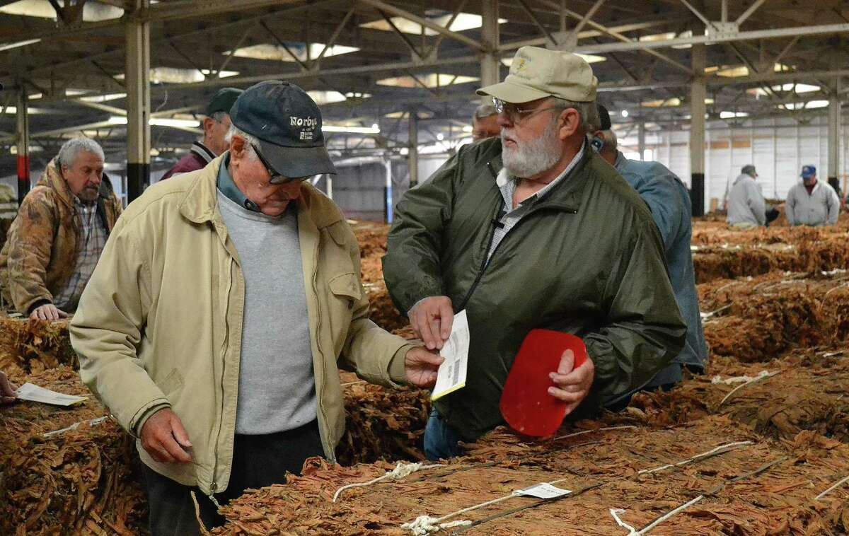 In this Nov. 18, 2014, photo, auctioneer Tripp Foy, right, hands a tobacco purchase ticket to a buyer at an auction in Danville, Ky. Foy is one of the last tobacco auctioneers in the country.