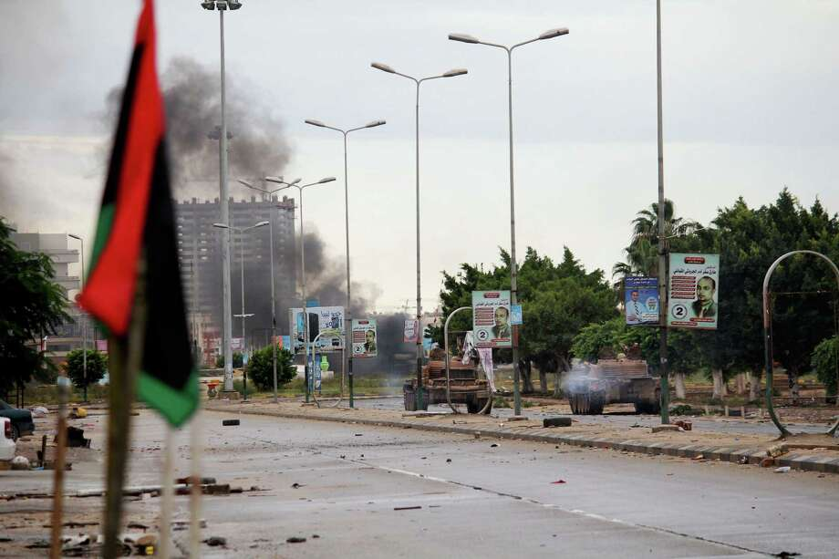 In this Wednesday, Oct. 29, 2014 photo, smoke rises during clashes between the Libyan military and Islamic militias in Benghazi, Libya. Government troops entered central Benghazi Wednesday after nearly 10 days of fighting Islamic extremist militias, a military spokesman said, in violence that killed dozens of people and forced hundreds of families to flee. (AP Photo/Mohammed El-Sheikhy) Photo: AP / AP