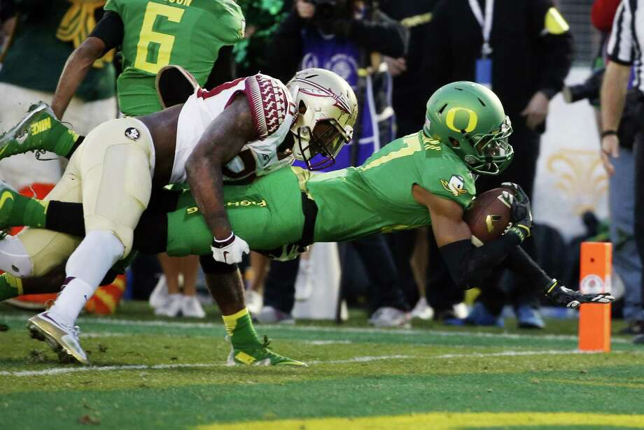 Oregon wide receiver Darren Carrington, right, scores as Florida State defensive back Trey Marshall tries to make the tackle during the second half Thursday. Photo: Lenny Ignelzi — The Associated Press  / AP