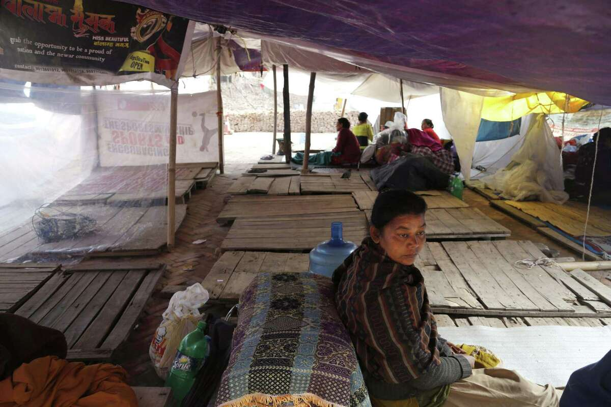 A Nepalese woman who lost her house in a strong earthquake sits at a makeshift camp on the side of a road in Kathmandu, Nepal, Friday, May 1, 2015. The strong magnitude earthquake shook Nepal on Saturday devastating the region and leaving some thousands shell-shocked and displaced. (AP Photo/Manish Swarup)