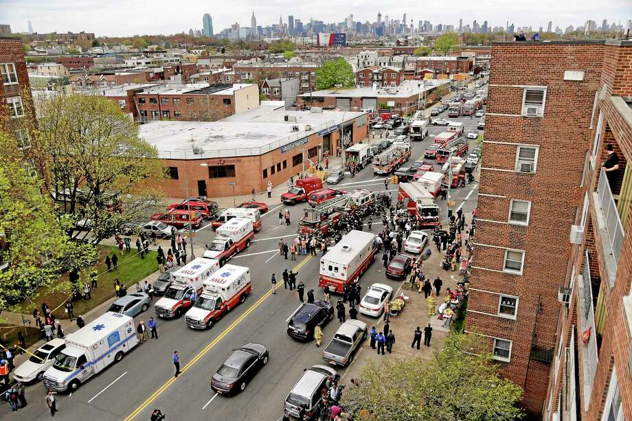 New York City emergency crews converge at 60th Street and Broadway to evacuate passengers from a subway train after it derailed in the Queens borough of New York, Friday, May 2, 2014.  The express F train was bound for Manhattan and Brooklyn when it derailed at 10:40 a.m. about 1,200 feet (365 meters) south of the 65th Street station, according to the Metropolitan Transportation Authority. Dozens of firefighters and paramedics with stretchers converged on Broadway and 60th Street, where passengers calmly left the tunnel through the sidewalk opening. A few were treated on stretchers. (AP Photo/Julie Jacobson) Photo: AP / AP