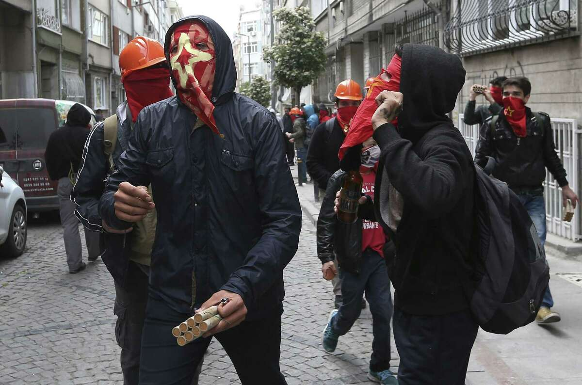 A demonstrator holds explosives during clashes with Turkish riot police officers in Istanbul, Turkey, Friday, May 1, 2015. The government assigned 30,000 police officers backed by helicopters as workers and demonstrators determined to defy a government ban, tried to march to iconic Taksim Square, where 35 people were killed during May Day celebration in 1977. (AP Photo/Emrah Gurel}
