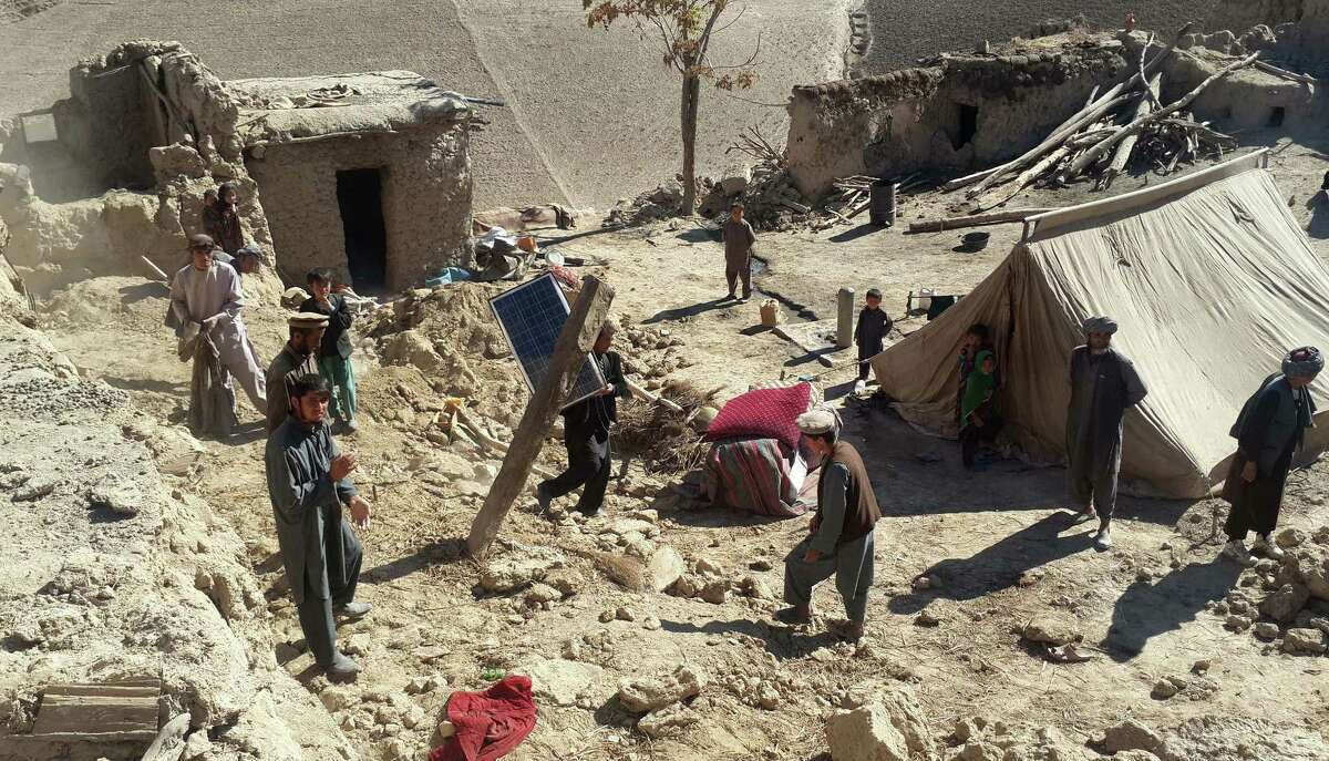Afghan men carry their belongings after an earthquake in Takhar province, northeast of Kabul, Afghanistan, Tuesday, Oct. 27, 2015. Rescuers were struggling to reach quake-stricken regions in Pakistan and Afghanistan on Tuesday as officials said the combined death toll from the previous day's earthquake rose to more than 300.