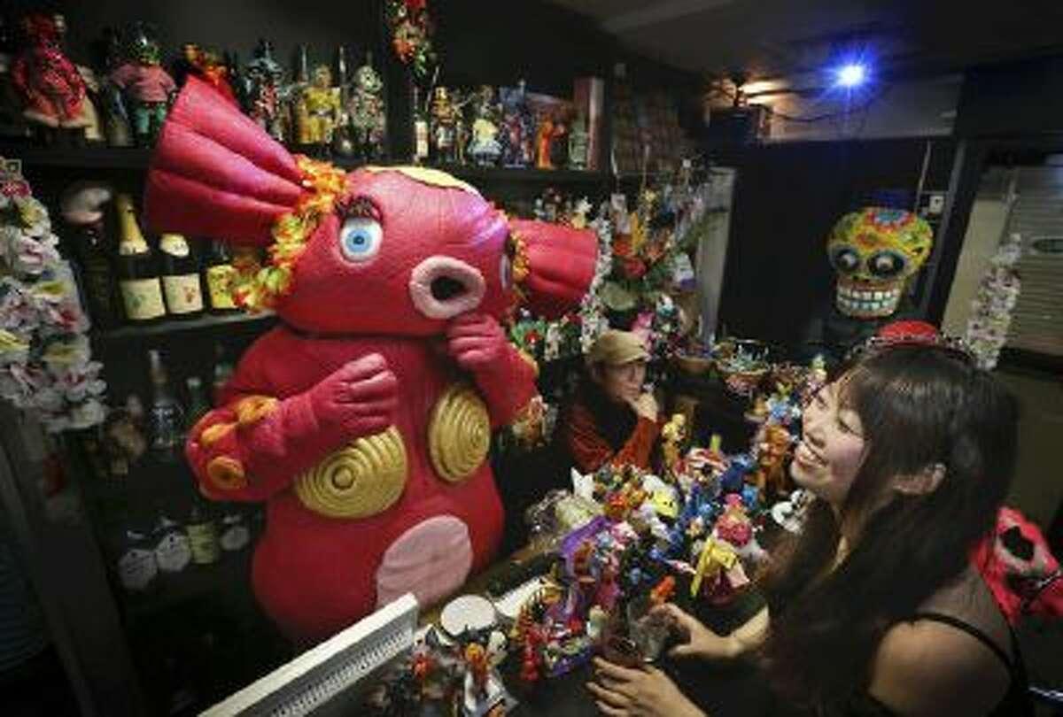 At a Tokyo bar, hostess monster Mucho welcomes a woman to the Dai-kaiju Saron.