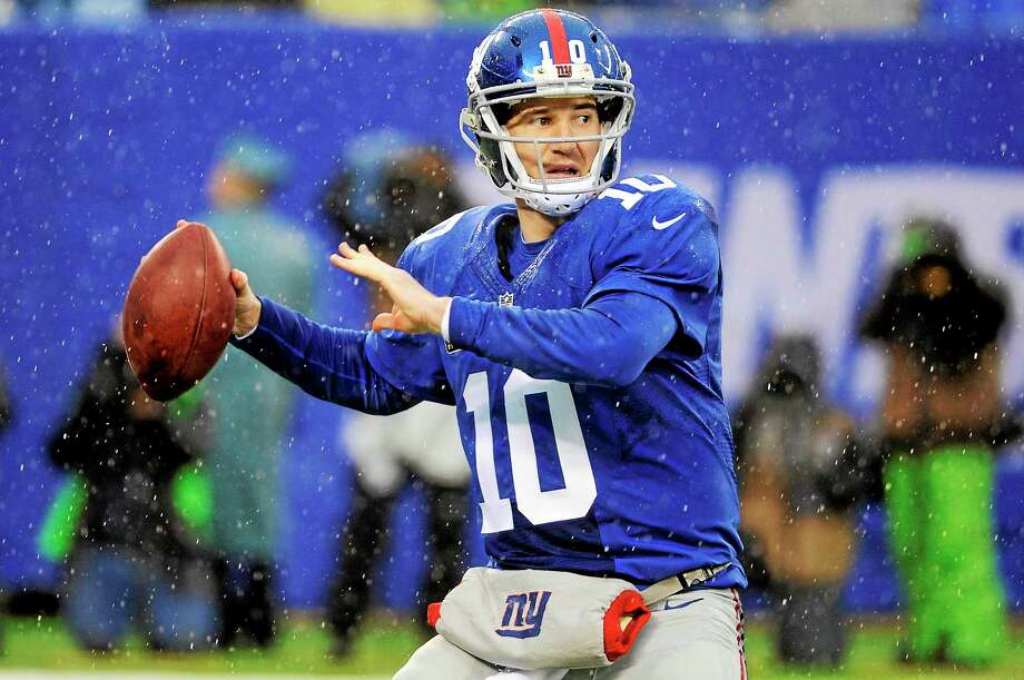 New York Giants quarterback Eli Manning will miss all the team's spring activities after recovering from ankle surgery. Photo: Bill Kostroun — The Associated Press  / AP2013