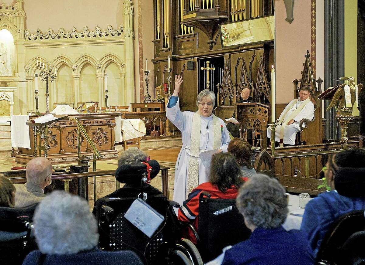 The Rev. Dana Campbell bestows blessings during an ecumenical service for homebound seniors at the Church of the Holy Trinity in Middletown.