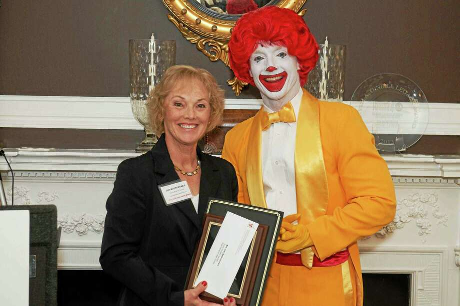 Retired East Hampton High teacher Joan Mastromonaco accepts a $1,000 grant for the school from Ronald McDonald. Photo: Submitted Photo  / (c)Nick Caito Photo