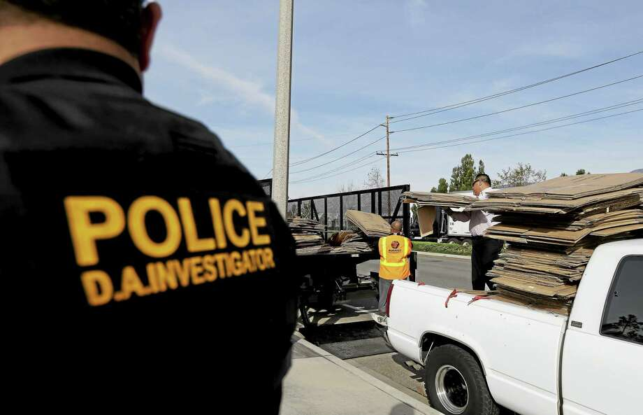 Steve Rivera, left, senior investigator with the San Bernardino County District Attorney's office, watches as a load of cardboard is seized temporarily in Fontana, Calif. The load was found to be legitimately given to the driver the by a local furniture store owner on the premise they'd split the recycling proceeds. Photo: Chris Carlson — The Associated Press  / AP