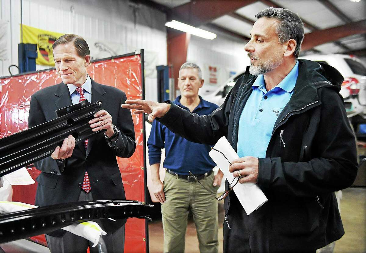 Anthony Ferraiolo, President of the Auto Body Association of Connecticut (ABAC) and owner of A & R Body Specialty & Collision Works, Inc. in Wallingford explains the difference between a factory-made part and an imitation to U.S. Senator Richard Blumenthal (D-Conn.) examines an imitation which is sold for $90 less, but inferior to the part made by Ford, Saturday, February 28, 2015. Body shop owners demonstrated the differences in quality and performance between the parts and to remind consumers that they have the right to choose where to repair their vehicles, regardless of recommendations from their auto insurer.