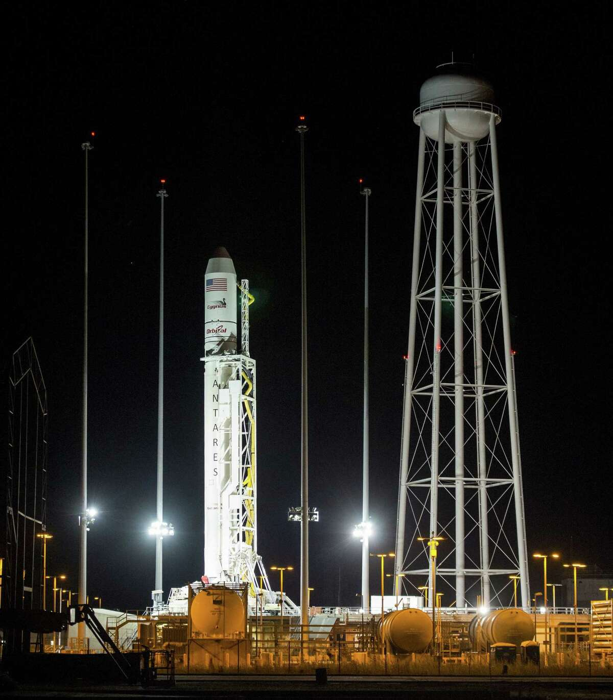 The Orbital Sciences Corporation Antares rocket, with the Cygnus spacecraft onboard, is seen after being raised into vertical position on launch Pad-0A, Oct. 25, 2014, at NASA's Wallops Flight Facility in Virginia.