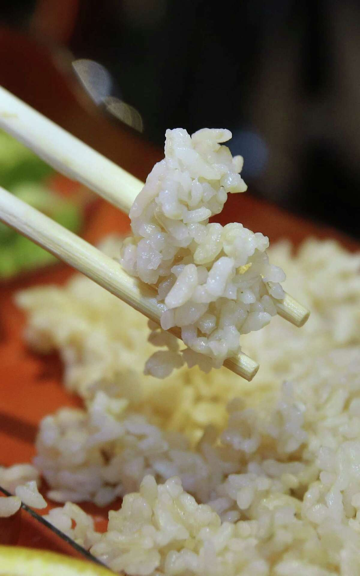 In this photo taken Friday, Oct. 10, 2014, a diner at Mikuni Restaurant digs into some rice while having lunch in Sacramento, Calif. California's historic drought is taking a bite out of the state's $5 billion rice industry, which exports to more than 100 counties and supplies nearly all American sushi restaurants. (AP Photo/Rich Pedroncelli)