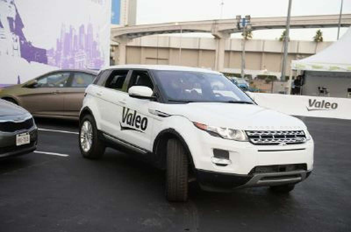 A Range Rover Evoque equipped with Valeo self-parking technology backs into a parking spot during a driverless car demo at the 2014 International CES in Las Vegas, Nevada, January 8, 2014. The driverless parking is initiated with an iPhone app. The car is equipped with 12 ultrasonic sensors, six in back and six in front, a laser scanner mounted in the grille, and four cameras.