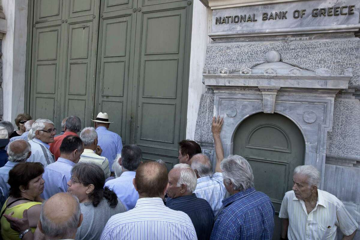 In this photo dated Monday, June 29, 2015, elderly people wait to receive their pensions outside the National Bank of Greece headquarters in Athens, as anxious Greek pensioners swarmed bank branches and lined up at ATMs. Following the referendum call by Prime Minister Alexis Tsipras and the ensuing decision by Greece's euro partners not to extend Greece's bailout beyond the end-June deadline, the Greek government announced a series of capital controls to prevent a bank run. The most onerous of the controls was a decision to cap daily withdrawals from ATMs at 60 euros.