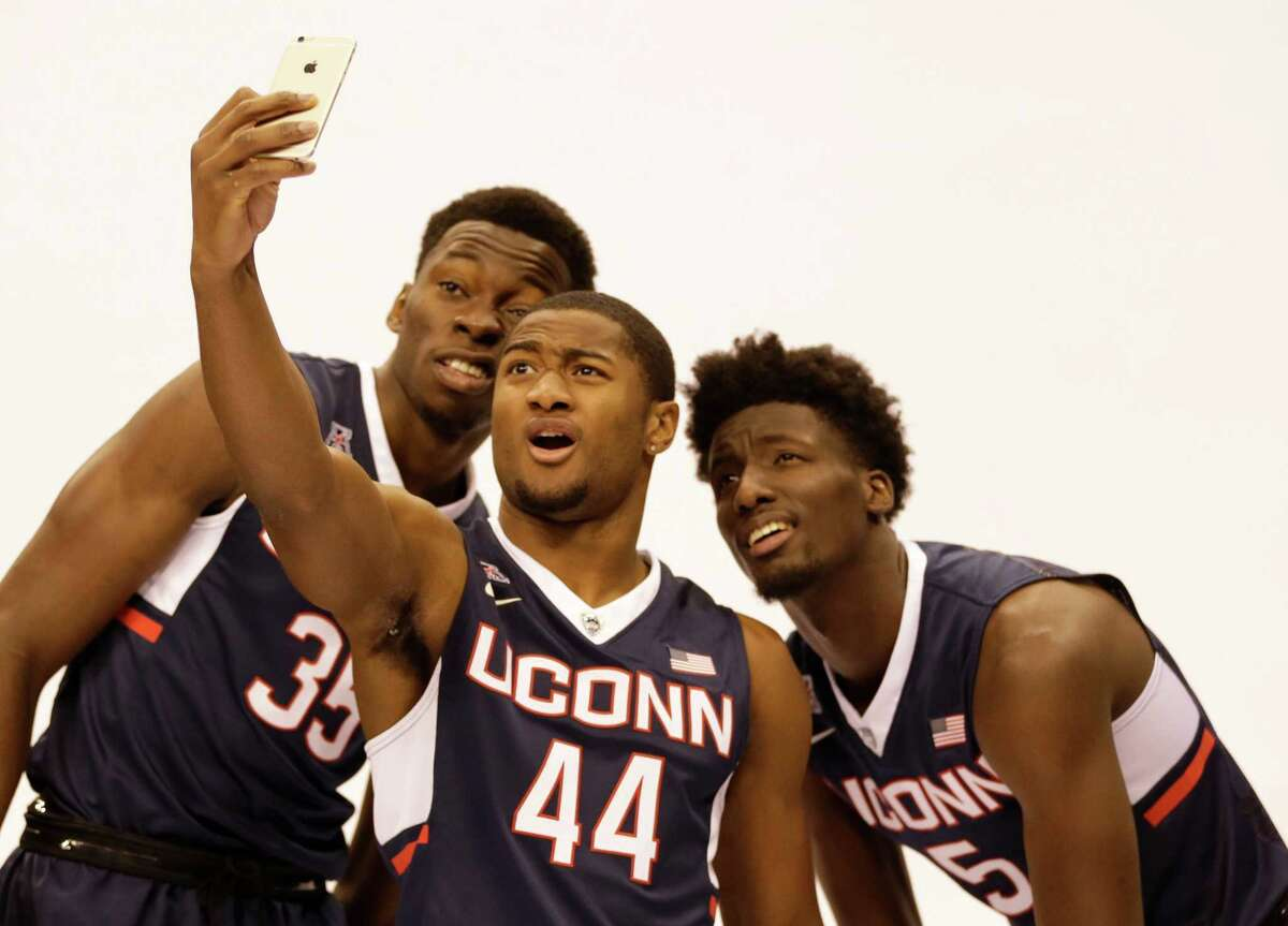 UConn players, from left, Amida Brimah, Rodney Purvis and Daniel Hamilton take a selfie during AAC media day on Tuesday in Orlando, Fla.