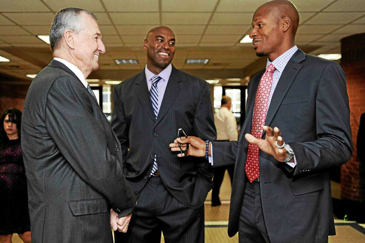 Southern Connecticut State men's basketball coach Scott Burrell, center, talks with former UConn coach Jim Calhoun, left, and Husky legend Ray Allen in 2013 in Storrs.