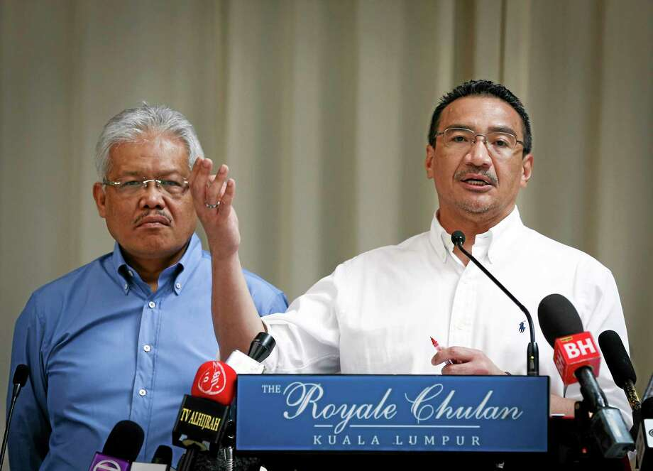 FILE- In this April 19, 2014 file photo, Malaysian Deputy Minister of Foreign Affairs Hamzah Zainudin, left, listens as Malaysia's acting Transport Minister Hishammuddin Hussein answers a question from a journalist during a press conference on the missing Malaysia Airlines Flight 370 at a hotel in Kuala Lumpur, Malaysia. Air traffic controllers did not realize that Malaysia Airlines Flight 370 was missing until 17 minutes after it disappeared from civilian radar, according to the preliminary report on the plane's disappearance released Thursday, May 1, 2014, by Malaysia's government. (AP Photo/Vincent Thian, File) Photo: AP / AP
