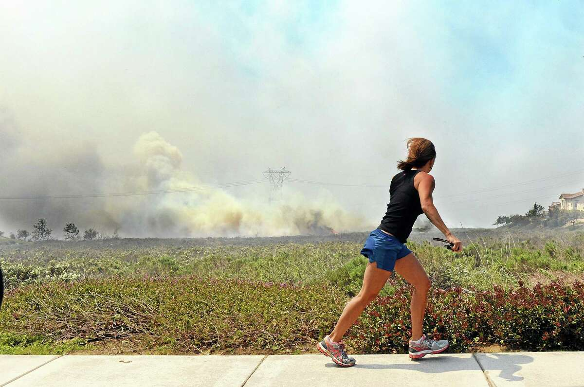 A resident talks on her phone as she watches the Etiwanda Fire in Rancho Cucamonga, Calif., Wednesday, April 30, 2014. The wildfire driven by surging Santa Ana winds sent a choking pall of smoke through foothill neighborhoods, forcing the evacuation of at least 1,650 homes and the closure of at least seven schools. No homes burned, but the smoke prompted mandatory evacuation orders for several areas of town nestled at the base of the San Bernardino Mountains east of Los Angeles. More than 500 firefighters battled the flames near this city of 165,000 people. The fire was reported about 8 a.m., grew to 200 acres by noon, quadrupled in size within a few hours and continued to grow as it roared through dry brush.(AP Photo/Inland Valley Daily Bulletin, Will Lester)