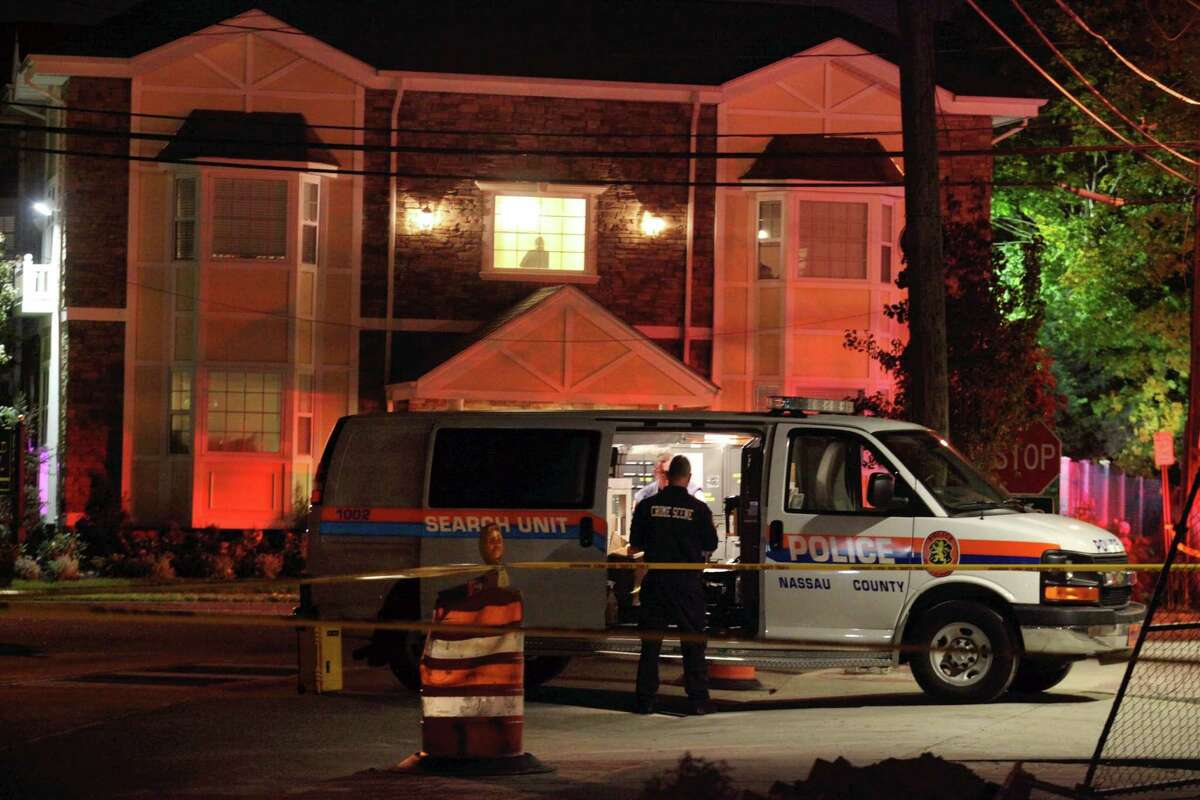 Nassau County police investigate a homicide in Farmingdale, N.Y., Tuesday, Oct. 28, 2014. Police are investigating the link between a woman killed at the Farmingdale apartment building and a man struck by a LIRR train at the nearby train station.
