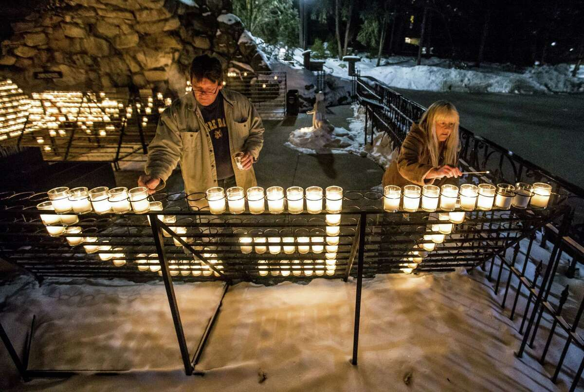 """William Michalski and his wife Rose Michalski, of South Bend, light votives that spell out """"TED"""" as the visit the Grotto of Our Lady of Lourdes on the campus of the University of Notre Dame following the death of former Notre Dame president Rev. Theodore M. Hesburgh, age 97, on Friday, Feb. 27, 2015, in South Bend, Ind. Rose Michalski has worked at Notre Dame for 31 years. (AP Photo/South Bend Tribune, Robert Franklin)"""