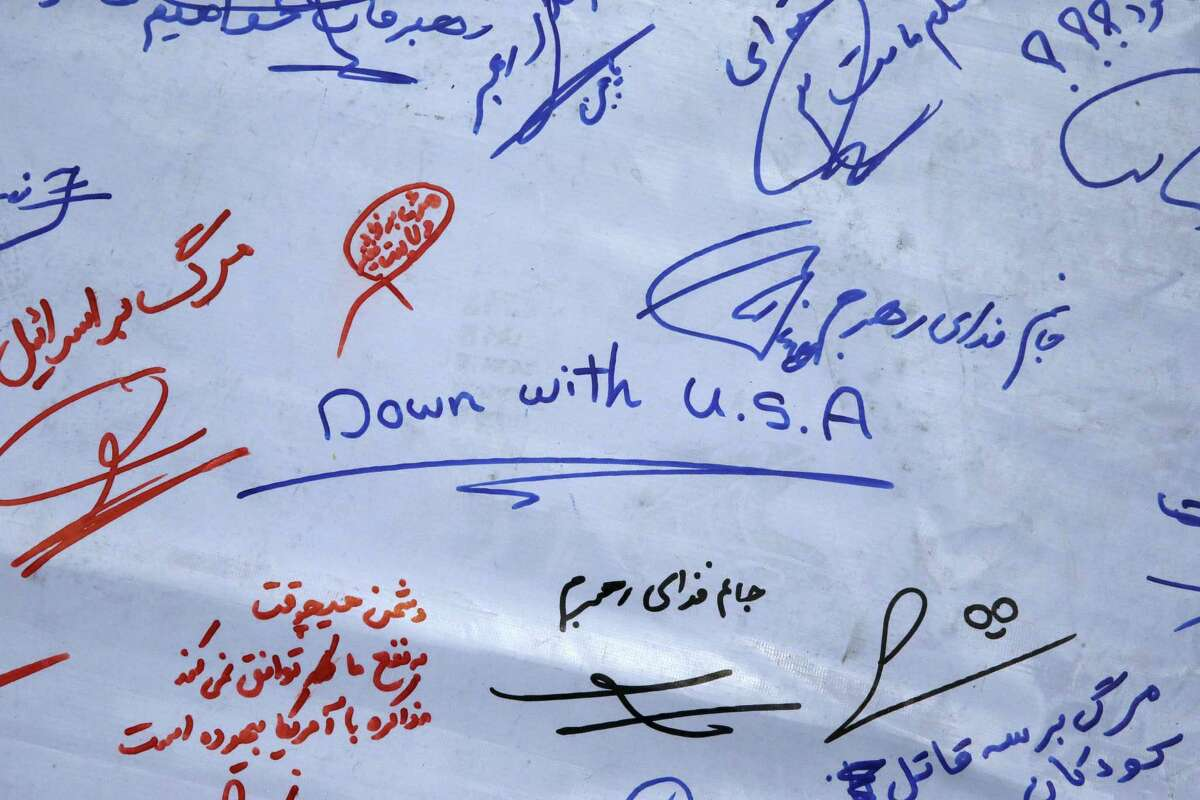 """A petition scroll with signatures and comments against the US and Israel and in support the Iranian supreme leader Ayatollah Ali Khamenei is displayed under the Azadi (Freedom) tower during a demonstration of a group of hard-liners demanding Iranian nuclear negotiators to sign a """"good deal"""" with 5+1 countries that reserves rights of the Iranian nation, in Tehran, Iran, Tuesday, June 30, 2015. Some 200 hard-liners gathered in a central square of Tehran providing a long petition in which they demanded all sanctions against Iran should be simultaneously lifted in the same time of signing the final nuclear deal and rejected any inspection on Iran's military sites saying the country should be able to continue its nuclear research and developments with no barrier."""