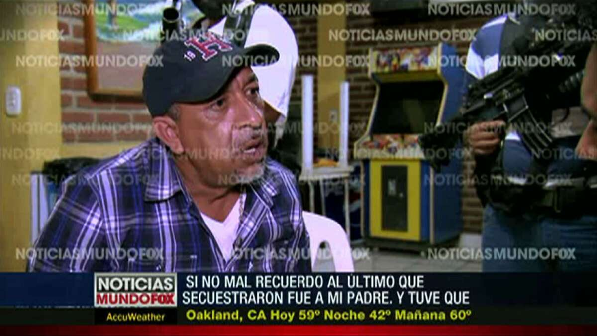 """In this frame grab from a Dec. 2013 file video interview by Mundo Fox via APTN, shows Servando """"La Tuta"""" Gomez,"""" leader of the Knights Templar cartel, giving an interview as masked and armed men watch in an unknown location in Mexico's Michoacan state. Gomez, one of Mexico's most-wanted drug lords, was captured early Friday, Feb. 27, 2015 by federal police in the capital city of Morelia, according to a Mexican official. Watermarks on the video were added by Mundo Fox. (AP Photo/Mundo Fox via APTN, File)"""