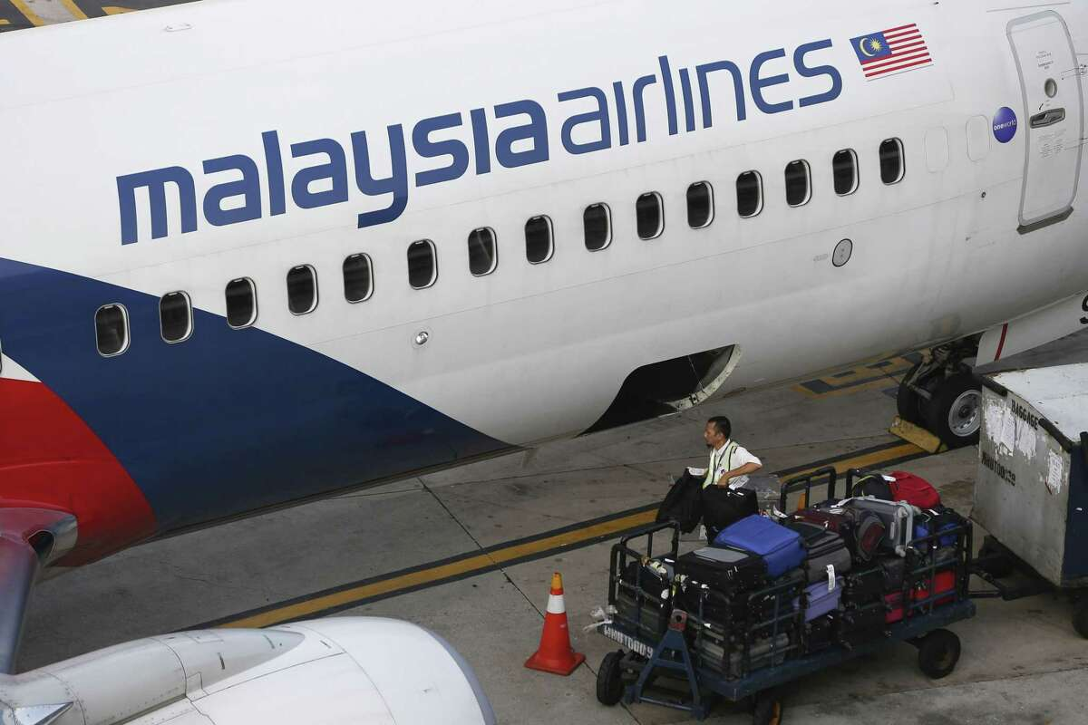 A Malaysia Airlines ground staff member unloads luggage from a plane at Kuala Lumpur International Airport in Sepang, Malaysia on June 1, 2015.