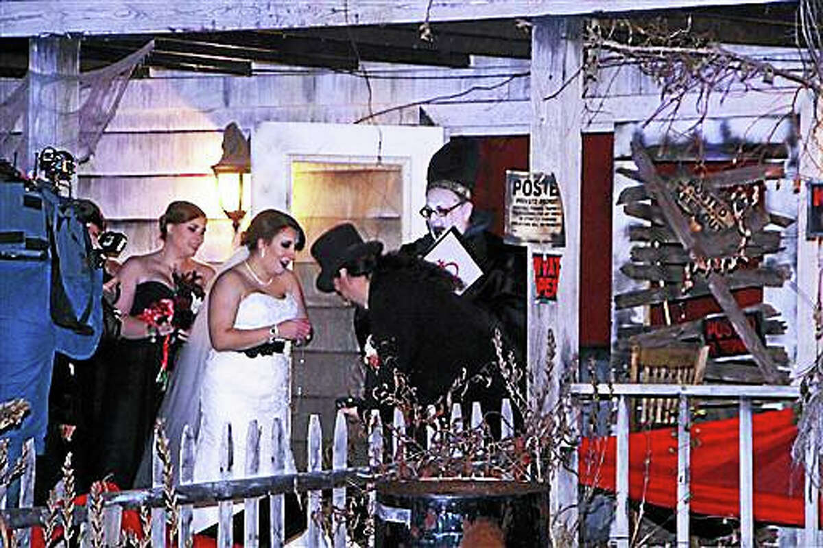 """In this photo provided by Spooky World Presents Nightmare New England, Melissa Cote and Tom Cowen, who both work at Spooky World Presents Nightmare New England in Litchfield, N.H., were married the night of Monday, Oct. 26, 2015, in front of the attraction's haunted house. During the ceremony, the justice of the peace encouraged them to """"haunt and howl at the moon together as long as you shall live,"""" and """"to have and to hold from this night on, in madness and in haunting fun."""""""