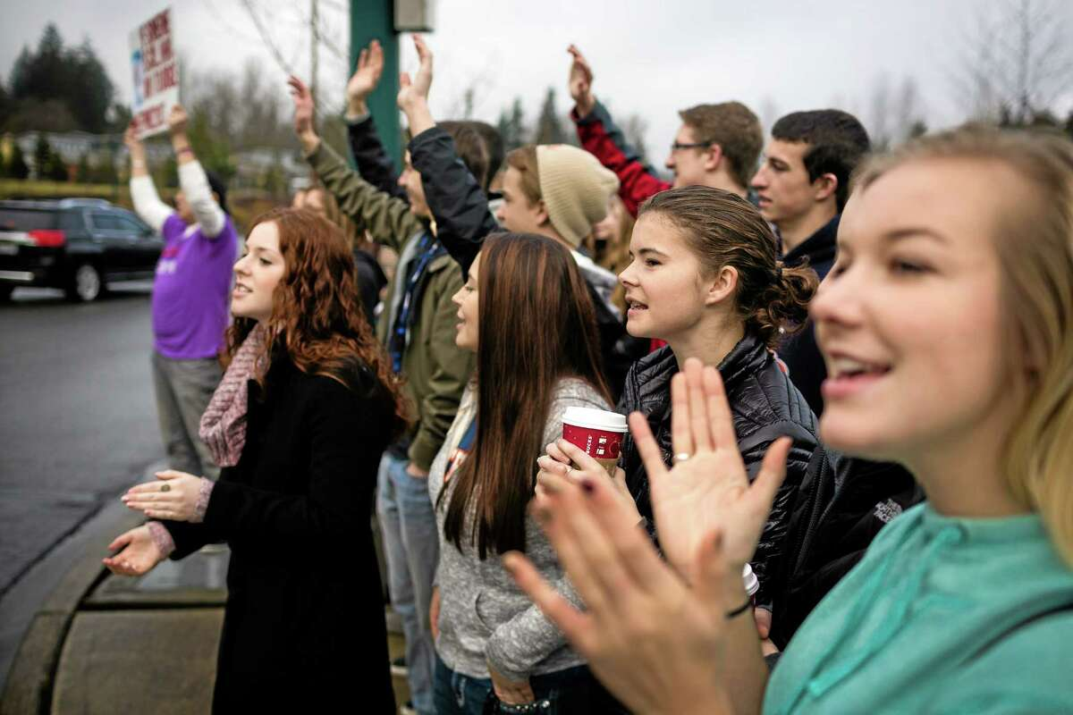 A crowd of nearly 30 students and supporters rally for former Eastside Catholic Vice Principal Mark Zmuda, who resigned his position after officials with the Archdiocese discovered that he was in a same-sex marriage and said he violated his contract, Saturday, Dec. 28, 2013, outside the school in Sammamish, Wash. (AP Photo/seattlepi.com, Jordan Stead)