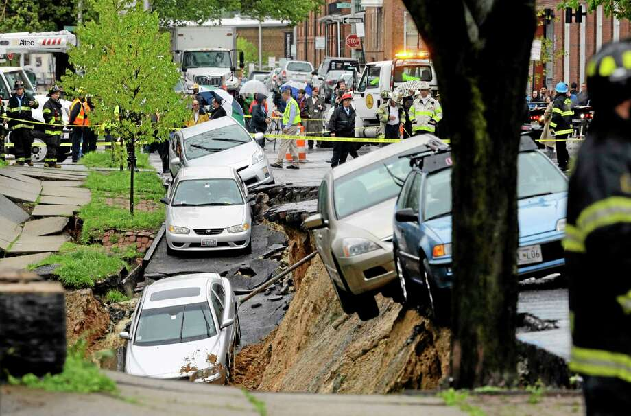 Cars sit on the edge of a sinkhole in the Charles Village neighborhood of Baltimore, Wednesday, April 30, 2014, as heavy rain moves through the region. Road closures have been reported due to flooding, downed trees and electrical lines elsewhere in the Mid-Atlantic. The National Weather Service issued flash flood warnings through Wednesday afternoon in Washington, northern Virginia and central Maryland. (AP Photo) Photo: AP / AP