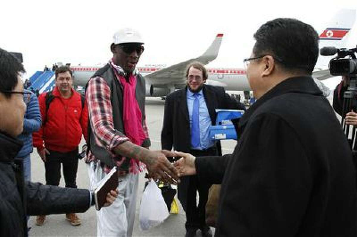 Former NBA basketball star Dennis Rodman shakes hands with North Korea's Sports Ministry Vice Minister Son Kwang Ho upon his arrival at the international airport in Pyongyang, North Korea.