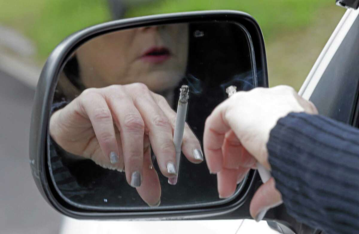 File — A woman smokes a cigarette while sitting in her truck in Hayneville, Ala.