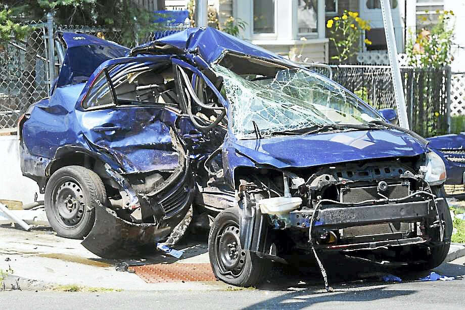 The scene at the intersection of Iranastan and Railroad avenues following a fatal accident involving a Toyota Yaris, pictured here, which was hit by another vehicle, not pictured, which was being pursued by state police in Bridgeport, Aug. 10, 2017. Photo: Ned Gerard / Hearst Connecticut Media