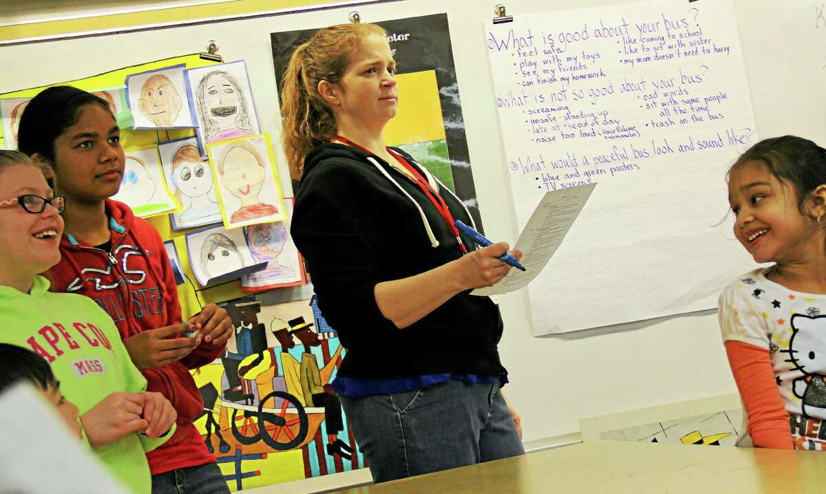 Teacher Carrie Nelson works with students on Friday at Lawrence Elementary School during the Peaceful Bus program.
