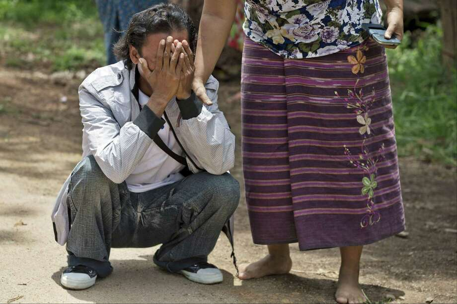 ADVANCE FOR RELEASE WEDNESDAY, JULY 1, 2015, AND THEREAFTER - In this May 16, 2015 photo, former slave fisherman Myint Naing, left, cries as he sees his mother running toward him as they are reunited after 22 years in their village in Mon State, Myanmar. Myint, 40, is among hundreds of former slave fishermen who returned to Myanmar following an Associated Press investigation into the use of forced labor in Southeast Asiaís seafood industry. (AP Photo/Gemunu Amarasinghe) Photo: AP / AP