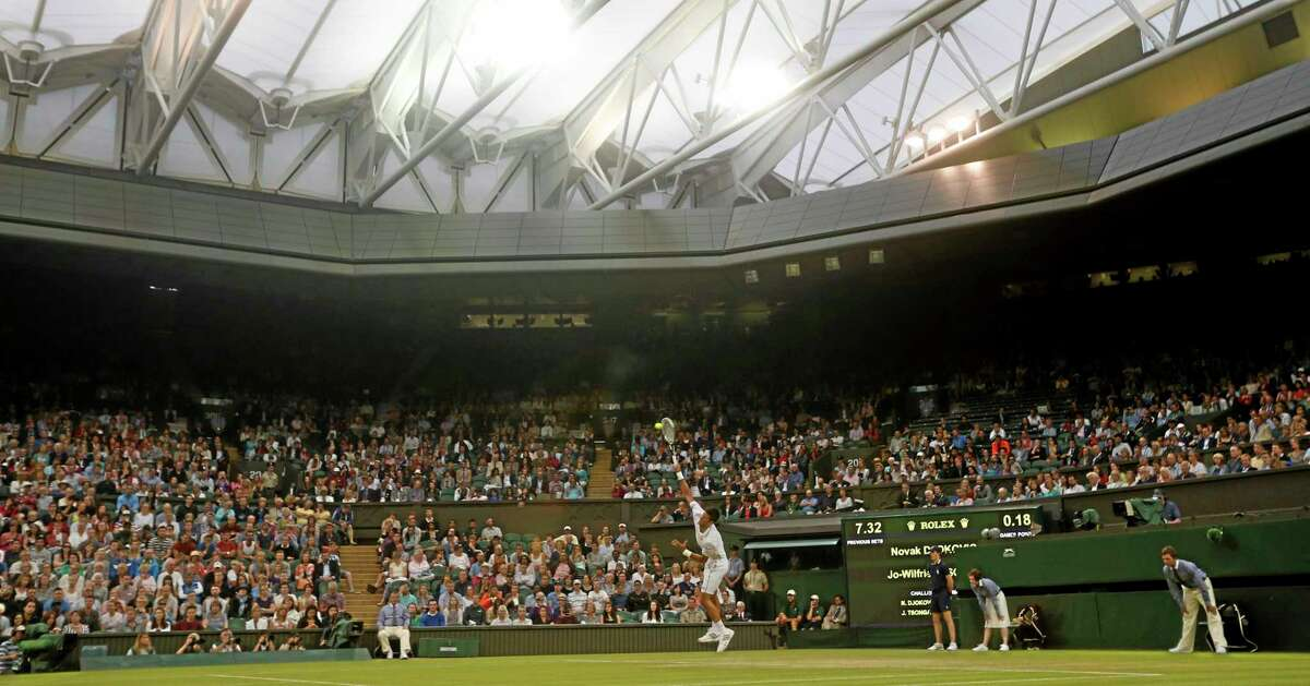 Novak Djokovic serves to Jo-Wilfried Tsonga during their singles match Monday at the All England Lawn Tennis Championships in Wimbledon, London. The match was played on Centre Court under the roof due to the weather.
