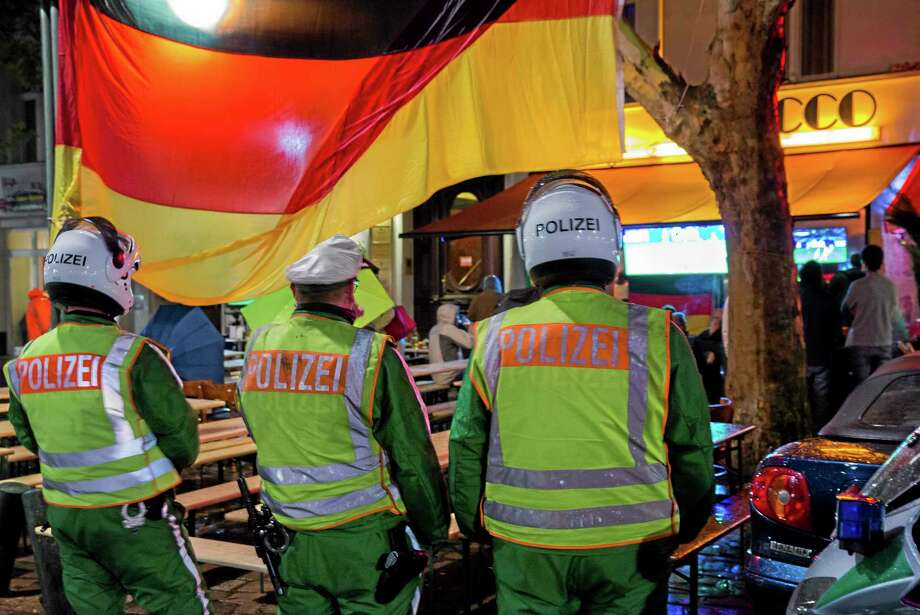 German motorbike policemen secure the area as they wait for the end of the World Cup Round of 16 match between Germany and Algeria on Monday outside a restaurant in Berlin, Germany. Photo: Gero Breloer — The Associated Press  / AP