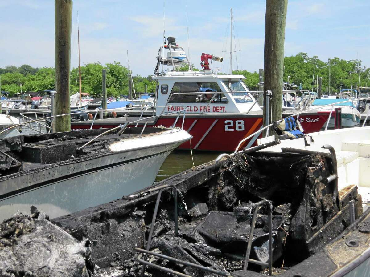 This photo provided by the Fairfield Fire Dept. shows two boats, foreground, that were destroyed in a marina fire. Officials say the fire broke out Sunday, June 29, 2014 at the South Benson Marina in Fairfield, Conn.