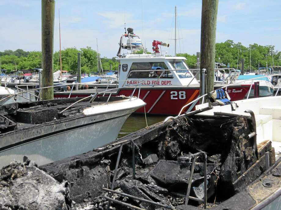 This photo provided by the Fairfield Fire Dept. shows two boats, foreground, that were destroyed in a marina fire. Officials say the fire broke out Sunday, June 29, 2014 at the South Benson Marina in Fairfield, Conn. Photo: (AP Photo/Fairfield Fire Dept., Jen Smith) / Fairfield Fire Dept.