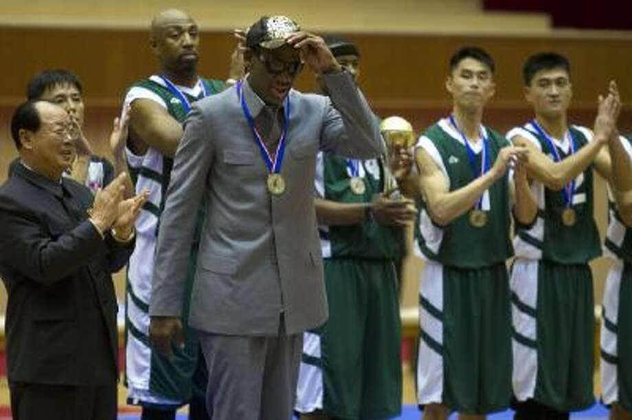 Dennis Rodman tips his hat as U.S. and North Korean basketball players applaud.