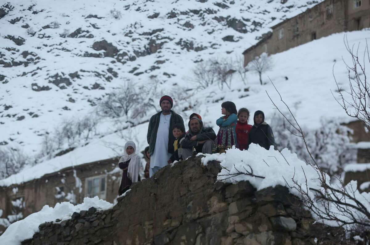 Afghan villagers look on in a village close to an avalanche site in Panjshir province north of Kabul, Afghanistan, Wednesday, Feb. 25, 2015. Avalanches caused by a heavy winter snow killed at least 124 people in northeastern Afghanistan, an emergency official said Wednesday, as rescuers clawed through debris with their hands to save those buried beneath. (AP Photo/Massoud Hossaini)