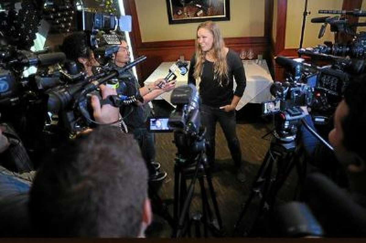 UFC women's bantam weight champion Ronda Rousey smiles while speaking with the media at Fleming's Prime Steakhouse & Wine Bar in Los Angeles Wednesday.