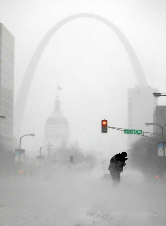 FILE - In this Sunday, Jan. 5, 2014, file photo, a person struggles to cross a street in blowing and falling snow as the Gateway Arch appears in the distance, in St. Louis. The deep freeze that gripped much of the nation this week wasn't unprecedented, but with global warming we're getting far fewer bitter cold spells, and many of us have forgotten how frigid winter used to be. (AP Photo/Jeff Roberson, File) Photo: AP / AP