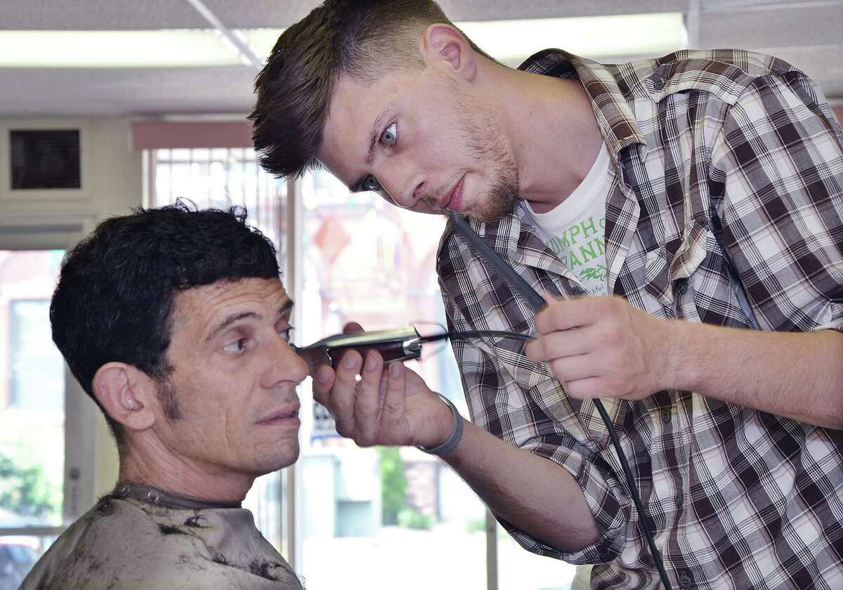 Cromwell resident Semso Cecunjanin gives Sebby Logiudice a haircut Monday afternoon at Semmy's Barber Shop at 125 Washington St., next door to KidCity in Middletown. Semmy's is opened 7 days a week from 9 a.m. to 7 p.m. and is offering $10 for the first haircut, $10 haircuts for kids and $14 for adults.