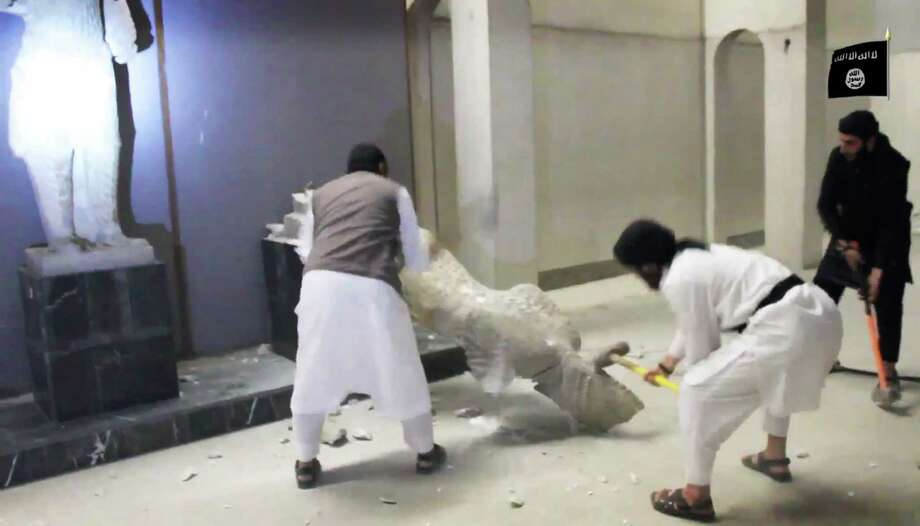 In this image made from video posted on a social media account affiliated with the Islamic State group on Thursday, Feb. 26, 2015, which has been verified and is consistent with other AP reporting, militants take sledgehammers to an ancient artifact in the Ninevah Museum in Mosul, Iraq. The extremist group has destroyed a number of shrines --including Muslim holy sites -- in order to eliminate what it views as heresy. The militants are also believed to have sold ancient artifacts on the black market in order to finance their bloody campaign across the region. (AP Photo via militant social media account) Photo: AP / Militant Video