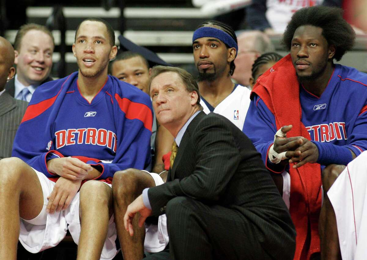 In this April 26, 2006 photo, Detroit Pistons coach Flip Saunders, front, and players, from left, Tayshaun Prince, Richard Hamilton and Ben Wallace watch the final minutes of Game 2 of their Eastern Conference first-round NBA playoff basketball game against the Milwaukee Bucks in Auburn Hills, Mich.