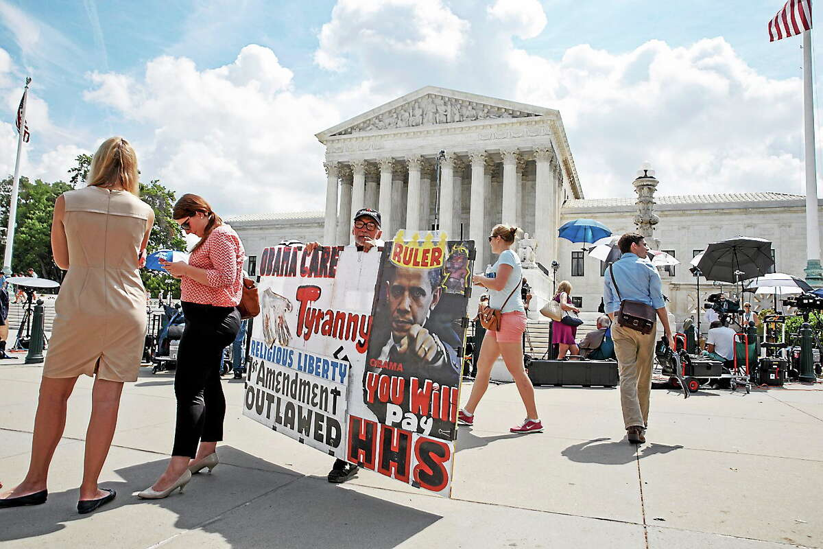 (AP Photo/J. Scott Applewhite) Protestors, press and passersby wait for decisions in the final days of the Supreme Court's term, in Washington on June 25, 2014. The Hobby Lobby chain of arts-and-crafts stores does not want to provide insurance coverage for certain forms of contraception that it finds objectionable on religious grounds.